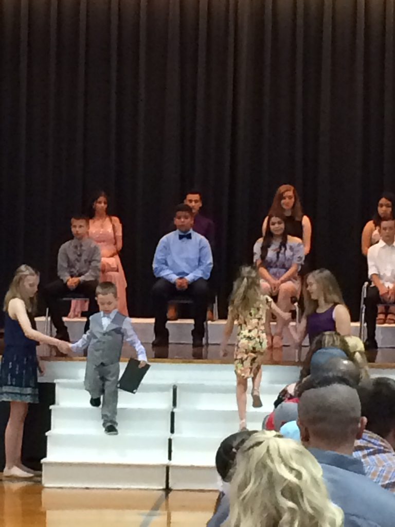 Kindergarteners receiving diplomas.