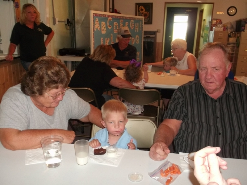 Grandparents enjoying a snack with their grandson.